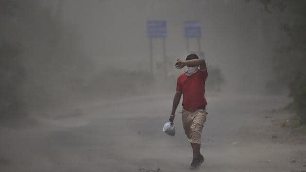 A man covers his face during dust storm in India, on Sunday, May 10, 2020.(Burhaan Kinu/HT PHOTO)