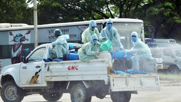 Health workers in PPE kits sanitizing the street around Sarusajai Quarantine centre in Guwahati on Sunday.(ANI)