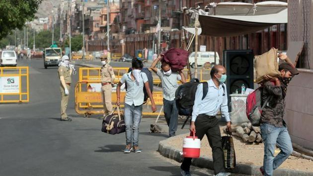 People carrying luggage pass barricades placed at the Ramganj coronavirus hotspot in Jaipur, Rajasthan.(Himanshu Vyas/ Hindustan Times)
