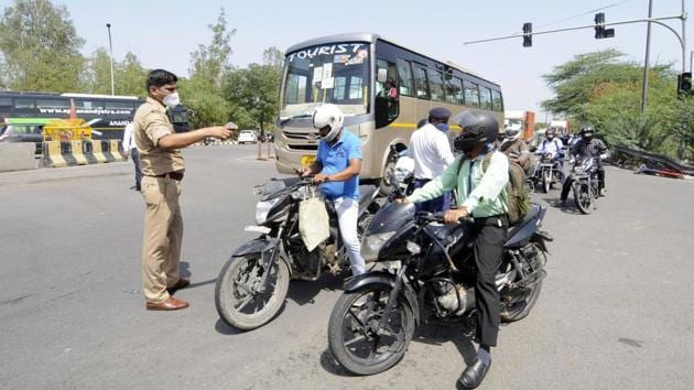 Uttar Pradesh Police personnel screen commuters at Delhi border after it was sealed, during the nationwide lockdown, at Mayur Vihar on Saturday.(Sunil Ghosh/HT Photo)