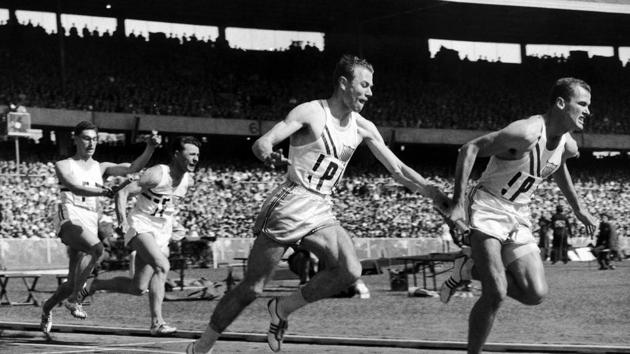 FILE - In this Nov. 30, 1956, file photo, Thane Baker, of the United States, hands to Bobby Joe Morrow for the last baton change in the first heat of the first round of the 4 x 100 meters Summer Olympic Games relay event in Melbourne, Australia. Morrow, the Texas sprinter who won three gold medals in the 1956 Melbourne Olympics while a student at Abilene Christian University, died Saturday, May 30, 2020. He was 84.(AP)