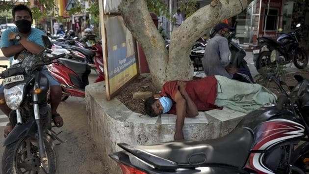 A man sleeps wearing a face mask beneath a tree by the side of a road during the coronavirus pandemic. 20 of the new cases in Assam have been traced to people who had recently travelled to the state by flights.(AP)