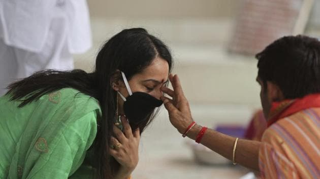 A priest applies vermilion paste on the forehead of a devotee at Kheer Bhawani temple amid the coronavirus pandemic in Jammu, on Saturday.(AP Photo)