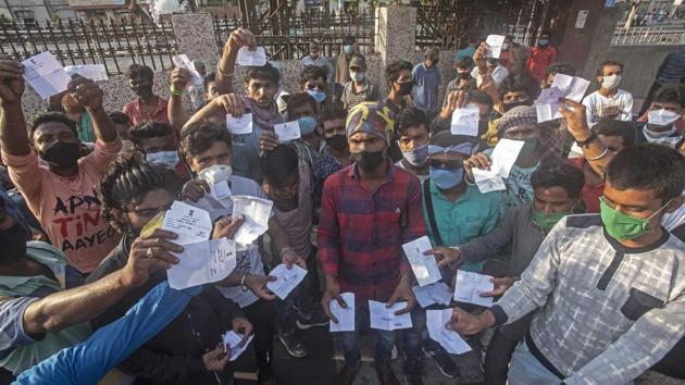 Migrants who were left behind show the tokens allotted to them on Saturday.(Pratham Gokhale/HT Photo)