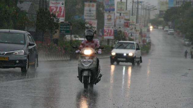Commuters caught unawares during a short spell of pre-monsoon rain at Dehu-Alandi road, Moshi, on Sunday.(HT PHOTO)