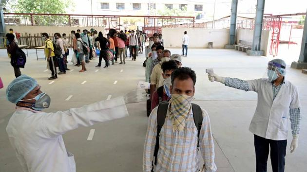 Uttar Pradesh: Medics conduct thermal screening of migrants arriving from Maharashtra by a special train during a government-imposed nationwide lockdown as a preventive measure against coronavirus in Prayagraj.(ANI)