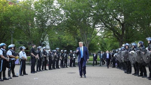 US President Donald Trump pumps his fist toward police as he walks between lines of riot police in Lafayette Park across from the White House while walking to St John's Church for a photo opportunity during ongoing protests over racial inequality in the wake of the death of George Floyd while in Minneapolis police custody, at the White House in Washington, US.(REUTERS)
