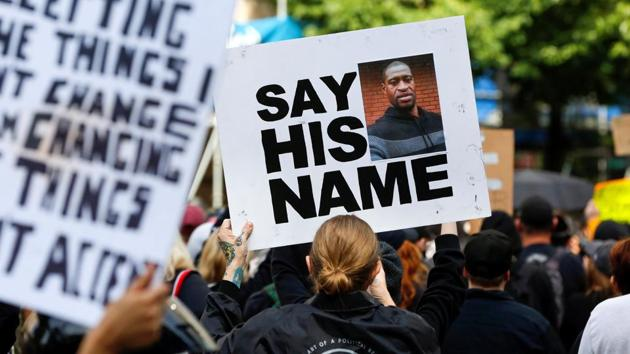 A protester holds a placard during a rally against the death in Minneapolis police custody of George Floyd, in Portland, Oregon, US.(REUTERS)