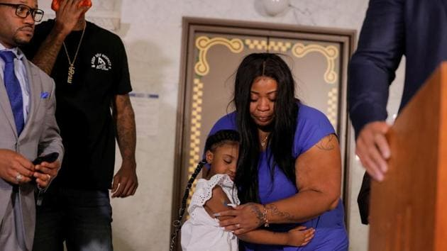 George Floyd's 6-year-old daughter, Gianna (in white), embraces her mother Roxie Washington before speaking about her father, at the Minneapolis City Hall, on Tuesday.(Reuters Photo)