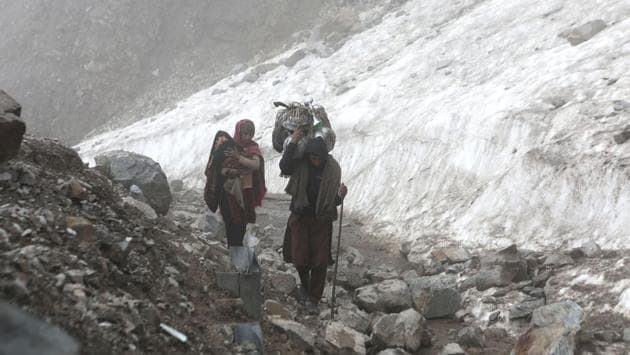 A Bakarwal woman with a child and a man carrying a bundle of utensils cross a rocky mountain pass on their way down to greener pastures. The division of labour tends to split household chores and running camps into the women's share while the men tend to the animals, take care of security and engage in seasonal tourism related jobs. (Waseem Andrabi / HT Photo)
