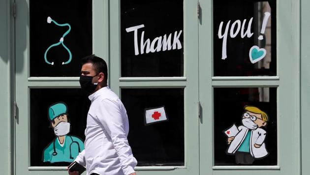 A man wearing a protective face mask walks past an Irish bar with drawings paying tribute to medical staff amid the coronavirus disease outbreak, in central Brussels, Belgium June 3, 2020.(Reuters File Photo)