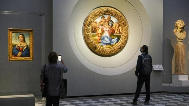 """Members of the media admire 15th century painting """"Doni Tondo"""" by Michelangelo Buonarroti, during a press tour of the Uffizi museum on the day off its reopening, in Florence, Wednesday, June 3, 2020. The Uffizi museum reopened to the public after over two months of closure due to coronavirus restrictions.(AP)"""