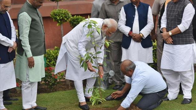 In this file photo, Prime Minister Narendra Modi plants a sapling as part of a plantation campaign, in the presence of Lok Sabha speaker Om Birla, Defence Minister Rajnath Singh and other Members of Parliament, at Parliament House, in New Delhi, on Friday, July 2019.(Raj K Raj/HT PHOTO)