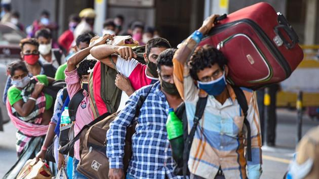 Migrants stand in a queue at Central Railway Station to board a Shramik Special train for West Bengal during ongoing Covid-19 lockdown.(PTI)