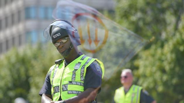 A flag, bearing a leftist symbol associated with Antifa, is reflected behind a Boston Police officer during the Straight Pride Parade rally in Boston, Massachusetts, US.(REUTERS)