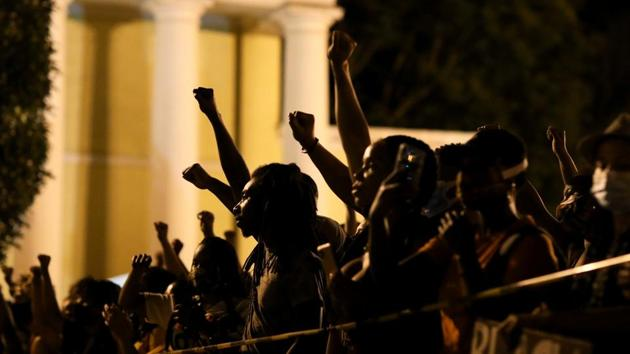 Demonstrators raise their fists in the air near the White House, during a protest against racial inequality in the aftermath of the death in Minneapolis police custody of George Floyd, in Washington, US.(REUTERS)