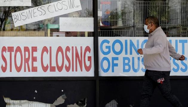 A man looks at signs of a closed store due to Covid-19 in US.(AP file photo)