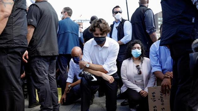 Canada's Prime Minister Justin Trudeau wears a mask as he takes a knee during a rally against the death in Minneapolis police custody of George Floyd, on Parliament Hill, in Ottawa, Ontario, Canada June 5, 2020.(REUTERS)