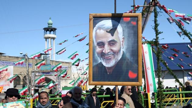 An Iranian man holds a picture of the late Iran's Quds Force top commander Qassem Soleimani, during the commemoration of the 41st anniversary of the Islamic revolution in Tehran, Iran.(REUTERS)