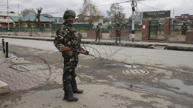 A paramilitary soldier stand guard near a temporary checkpoint during lockdown in Srinagar, India.(AP)
