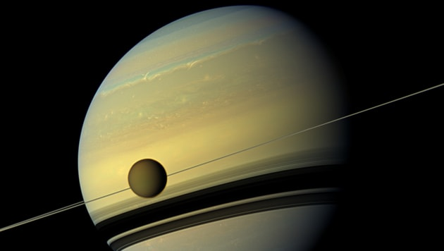 Saturn's moon Titan is seen here as it orbits the planet. Below Titan are the shadows cast by Saturn's rings. This natural color view was created by combining six images captured by NASA's Cassini spacecraft on May 6, 2012.(Photo Credit: NASA/ JPL-Caltech/Spac Science Institute)