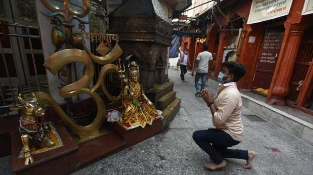 A devotee prays at the Kalkaji temple in New Delhi after it reopened on June 8 as part of measures constituting the first major step of an exit from lockdown. The face mask is now deemed battle worthy armour in reducing the risk of coronavirus transmission. (Biplov Bhuyan / HT Photo)