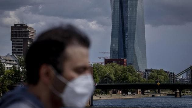 A man walks in front of the European Central Bank in Frankfurt, Germany. If the coronavirus re-emerges later in the year, however, the global economy could shrink 7.6%, the OECD said.(AP)