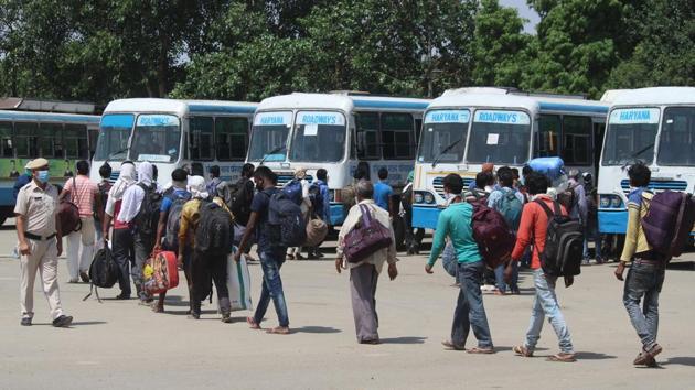 Migrants head to board Haryana Roadways buses that will ferry them to the railway station to board a Shramik Special train to Bihar's Darbanga.(Yogendra Kumar/HT PHOTO)