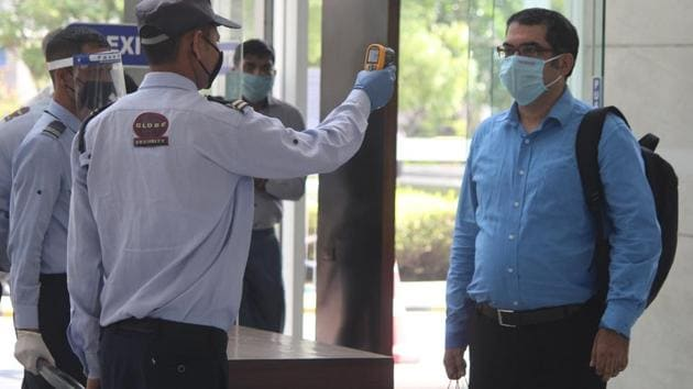 A security guard thermal screens people as they enter an office building in Gurugram on June 8. Beyond our homes, the beep of an infrared thermometer now grants or withholds access to any public space or experience. (Yogendra Kumar / HT Photo)