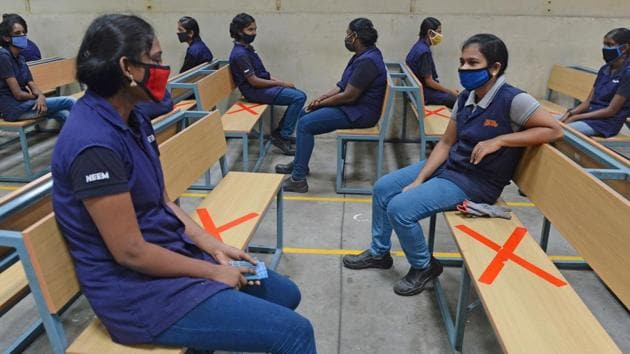 Industrial workers sit while maintaining social distancing at an assembly unit of Royal Enfield motorcycles in Oragadam on June 9. Relaxations have allowed for returns to workplaces albeit in fewer numbers but instinctual greetings such as handshakes remain too invasive even among friends or colleagues due to health concerns. (Arun Sankar / AFP)