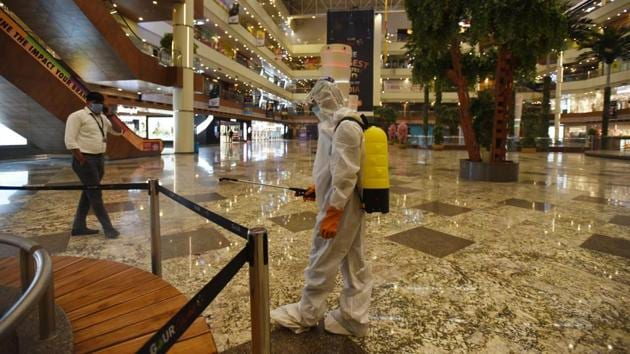 There is little alarm anymore at the sight of sanitation workers head to toe in PPE coveralls or with tanks strapped to their backs as they diligently go about disinfecting spaces for public use like here at Gaur City Mall in Greater Noida on June 9. (Virendra Singh Gosain / HT Photo)
