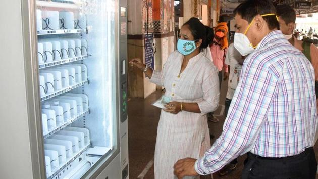 Travellers use a vending machine dispensing face masks and sanitizer rather than food or drink during an onward journey at Patna Junction on June 9. (Santosh Kumar / Ht Photo)
