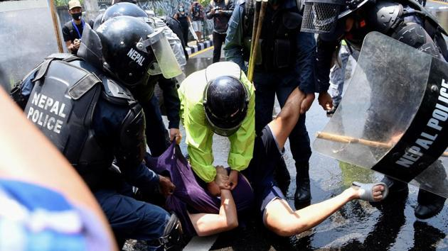 Police detain a person protesting against the government's policy on coronavirus. Tens of thousands of migrant workers have returned to Nepal from India and the Middle East after losing their jobs, reported AFP. (Prakash Mathema / AFP)
