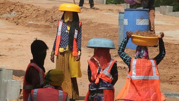 Women labourers in traditional attire and safety jackets use tagari pans to shield from the sun while working at the construction site of an elevated road, in Jaipur, Rajasthan on Wednesday.(Himanshu Vyas/HT Photo)