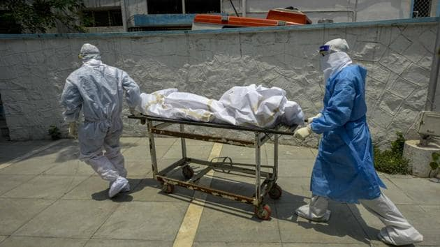 Medical professionals wearing PPE coveralls escorts the body of a coronavirus victim at a hospital in New Delhi.(Biplov Bhuyan/HT PHOTO)