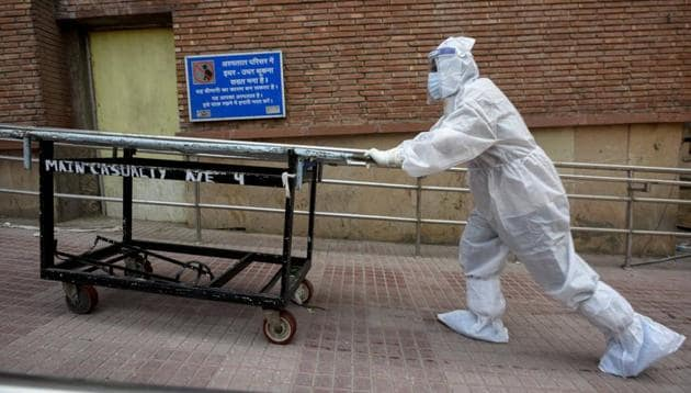 A Medical professional wearing PPE coveralls pushes a stretcher outside the Covid-19 ward at LNJP Hospital in New Delhi on Tuesday.(Biplov Bhuyan/HT PHOTO)