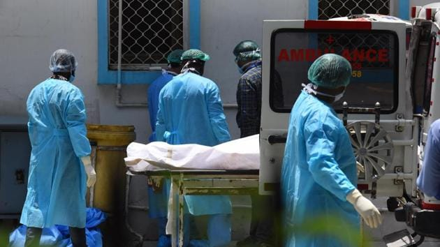 A medical team wheels out the body of a person who died of Covid-19 during a handover to family members outside the mortuary, at Lok Nayak Jai Prakash (LNJP) hospital in New Delhi on Thursday.(Raj K Raj/HT File Photo)