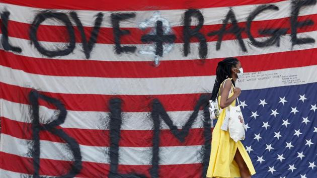 A woman walks in front of an upside down U.S. flag affixed to the Seattle Police Department East Precinct building at the self-proclaimed Capitol Hill Autonomous Zone (CHAZ) during a protest against racial inequality and call for defunding of Seattle police, in Seattle, Washington.(REUTERS)