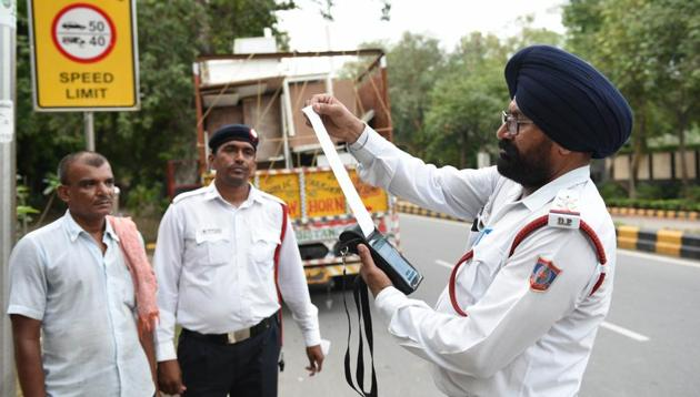 Police personnel issue a fine to a truck driver after the implementation of the amended Motor Vehicles Act that came into force on September 1, 2019.(Arvind Yadav/HT File Photo)