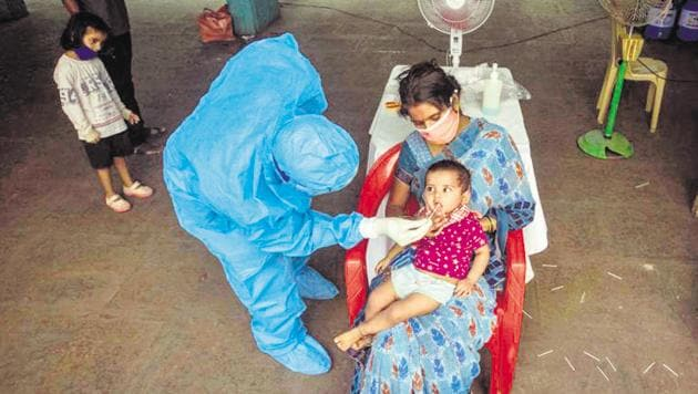 A healthcare worker collects an oral swab sample of a child for Covid-19 test, at Sane Guruji Smarak.(Pratham Gokhale/HT Photo)