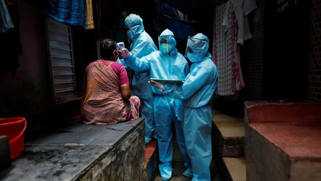 Healthcare workers wearing personal protective equipment (PPE) check the temperature of a resident at a slum during a check-up camp for the coronavirus disease (Covid-19) in Mumbai, India.(REUTERS)