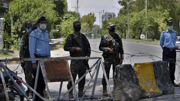 Pakistan paramilitary soldiers and a police officers stand guard at a checkpoint of a restricted area in Islamabad, Pakistan(AP File Photo)