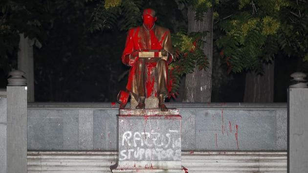 """A statue of Indro Montanelli, a one-time fascist who became and icon of Italy's right and a leading name in Italian journalism, is covered with red paint during a Black Lives Matter protest, in Milan, Italy, Saturday, June 13, 2020. Protesters want to remove the statue. White paint on the statue reads: """"Racist and rapist."""" (AP Photo/Antonio Calanni)(AP)"""