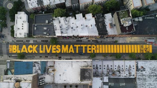 """A giant """"BLACK LIVES MATTER"""" sign is painted in orange on Fulton Street, Monday, June 15, 2020, in the Brooklyn borough of New York.(AP)"""