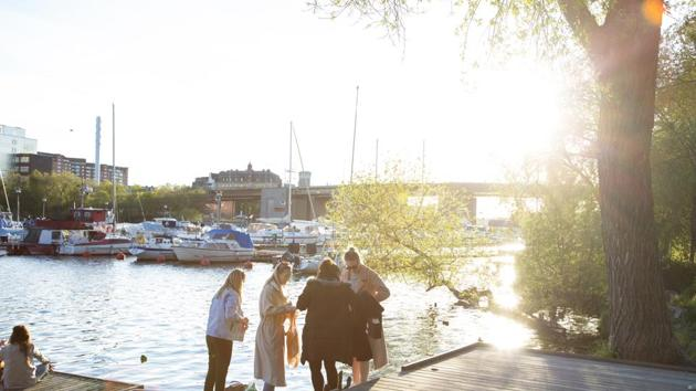 A group of people socialize on a jetty on the water's edge at Tantolunden in Stockholm, Sweden. Sweden says its approach was based on an assumption that Covid-19 will be around for a while yet, meaning severe temporary lockdowns will do little to prevent its spread in the long run.(Bloomberg)
