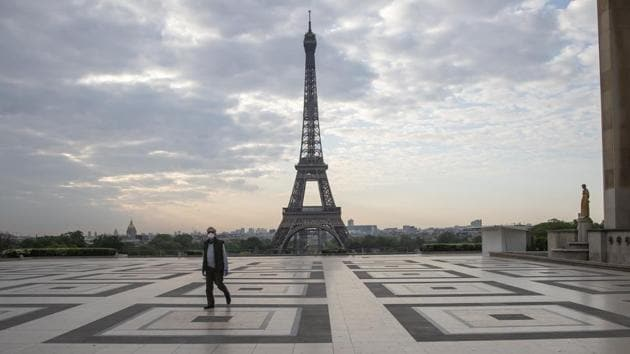 A man wears a mask to protect against the spread of the coronavirus as he walks along the Trocadero square in front of the Eiffel Tower in Paris.(AP)