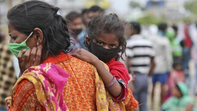 A woman carries a child as they wait with other migrant worker families to have their temperatures checked before being allowed to board a train tomorrow for their hometowns.(AP)