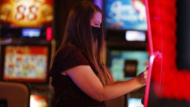 Alyssa Brunette hangs a sign on slot machine that will be not be used, in order to follow rules of social distancing, as she helps to prepare for the reopening of Monarch Casino and Resort after a three-month closure because of the spread of the new coronavirus Tuesday, June 16, 2020, in Black Hawk, Colo. Casinos in Black Hawk, nearby Central City and Cripple Creek have been granted approval from the state to open on a limited basis as coronavirus cases diminish in Colorado. (AP Photo/David Zalubowski)(AP)