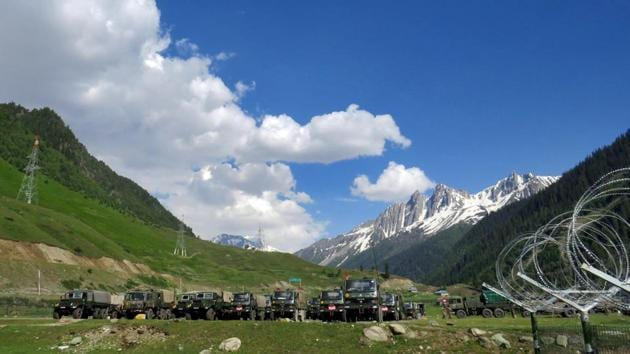 Indian army soldiers walk past their parked trucks at a makeshift transit camp before heading to Ladakh, near Baltal, southeast of Srinagar.(REUTERS)