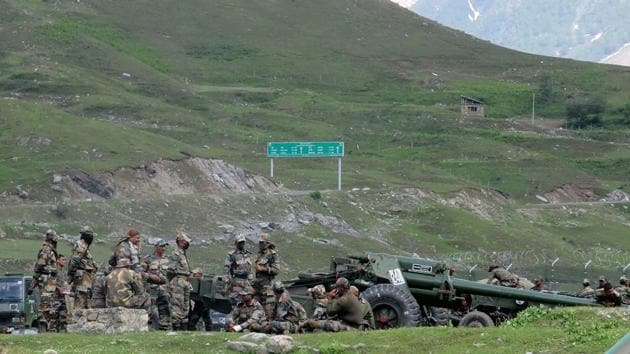 Indian army soldiers rest next to artillery guns at a makeshift transit camp before heading to Ladakh, near Baltal, southeast of Srinagar.(REUTERS)